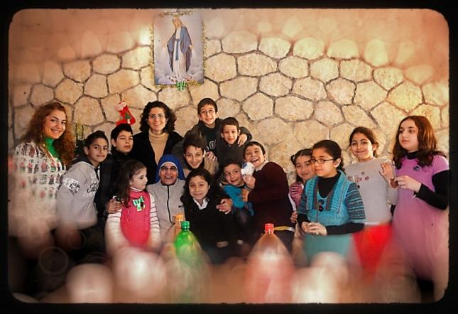 Jóvenes que ayudan con la escuelita y grupo de niños durante la fiesta de Navidad.