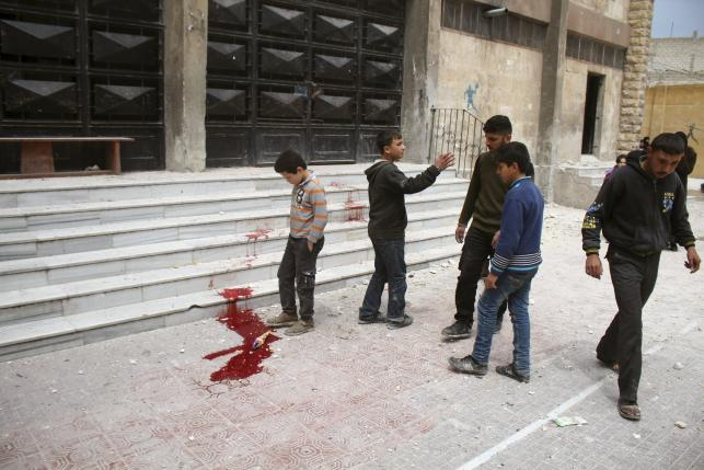 Residents inspect blood stains after what activists said was shelling by warplanes loyal to Syria's president Bashar Al-Assad on Saad Al-Ansari school in Aleppo's rebel-controlled Al-Mashad neighbourhood