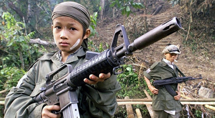 Children from the Karen National Union (KNU) insurgent army hold assault weapons during celebrations marking the 51st anniversary of the army's rebellion against the Myanmar Junta in Tak, near the border with Thailand 31 January 2000. Former leader of the KNU Bo Mya lost his position in vote of more than 100 members of the KNU and other anti-junta groups.   (ELECTRONIC IMAGE) AFP PHOTO/Pornchai KITTIWONGSAKUL