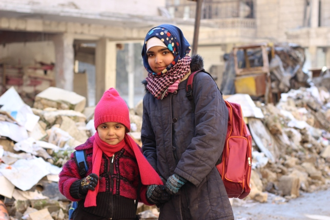 "On 29 January 2017 in the Syrian Arab Republic, Seedra (left), 6, and her sister Baraa stand outside their school on the first day of the second semester at the Kheir eddine Al-Asadi School in Sakhoor neighbourhood of eastern Aleppo. The third floor of the school building sustained heavy damage during the fighting and remains unusable. Approximately 600 children are squeezed into classrooms on the remaining two floors. UNICEF and its partners are conducting rapid assessment of school conditions in East Aleppo. Of the 422 schools, 217 are either destroyed, damaged or inaccessible. As of 31 January 2017, UNICEF has supported the re-opening of 23 primary schools in the eastern parts of Aleppo city over the past weeks, allowing nearly 6,500 children to return to school. UNICEF has provided school supplies, developed an accelerated learning programme and trained teachers to help displaced children catch up on the months and years of education they have missed. Ten prefabricated classrooms were also set up. An urgent awareness-raising programme has been rolled out to inform children and families about the dangers of unexploded remnants of war. So far the programme has reached 50,000 children. Psychosocial support activities have been provided to 35,000 children in shelters and other locations, to help them recover from the horrors they lived through. UNICEF provided ""schools in a box"" and recreational kits to 90,000 children in Idlib and west rural Aleppo. UNICEF-supported professional development courses benefitted 280 teachers. ""Getting children back to learning is one of our key priorities,"" said Hanaa Singer, UNICEF Representative in Syria. ""School provides children with a much needed sense of routine, and offers a place to learn, play, heal and reconnect with their childhood."" There is much more work to be done. An estimated 1.7 million children in Syria are currently out of school."
